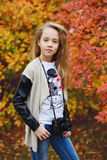 Pretty preteen girl. With old photocamera in fall time Royalty Free Stock Photography