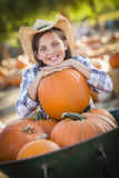 Pretty Preteen Girl Playing with a Wheelbarrow at the Pumpkin Patch. Preteen Girl Wearing Cowboy Hat Playing with a Wheelbarrow at the Pumpkin Patch in a Rustic Royalty Free Stock Photography