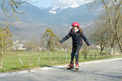 Pretty preteen girl on roller skates in helmet at a track. A  pretty preteen girl on roller skates in helmet at a track Royalty Free Stock Photo