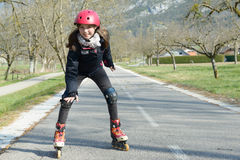 Pretty preteen girl on roller skates in helmet at a track. A pretty preteen girl on roller skates in helmet at a track Stock Image