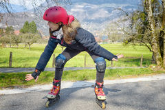 Pretty preteen girl on roller skates. In helmet at a track Royalty Free Stock Photography