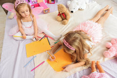 Pretty princess making images in bedroom. What are you drawing. Top view of two cute little sisters painting pictures. Child interested what illustration her stock images