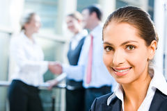 Pretty professional. Image of pretty professional with charming smile on the background of people's handshake royalty free stock photo