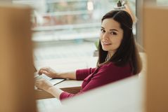 Pretty professional receptionist smiling while being at work. Peaceful glance. Cute clever young receptionist smiling while being at her comfortable workplace stock photos