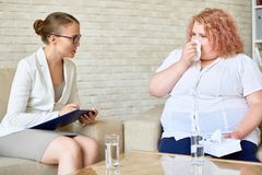 Pretty Psychologist at Work. Profile view of confident young psychologist taking notes on clipboard while consulting crying obese women during therapy session at stock image