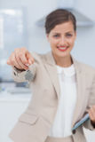 Pretty real estate agent offering house key Stock Image