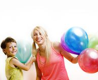 Pretty real family with color balloons on white background, blond woman with little boy at birthday party bright smiling stock photography