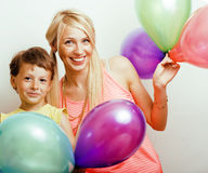 Pretty real family with color balloons on white background, blonde mother with cute son on birthday party celebration Royalty Free Stock Image