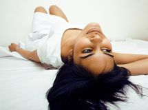 Pretty real mulatto brunette woman in bed, cant Stock Images