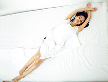 Pretty real mulatto brunette woman in bed, cant Royalty Free Stock Image