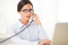 Pretty receptionist using the phone at workplace Stock Images