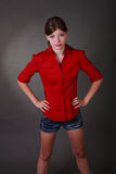 Pretty in Red. Studio shot of a pretty young girl with arms on her hips in exasperation wearing a red blouse and short shorts Royalty Free Stock Photography