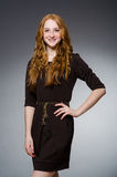 Pretty red hair girl in brown dress against gray Stock Photo