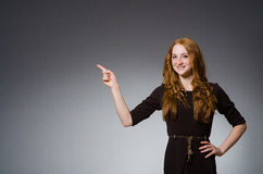 Pretty red hair girl in brown dress against gray Royalty Free Stock Photos