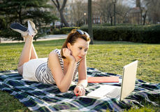 Pretty red hair woman working on laptop in park Stock Photo