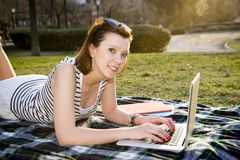 Pretty red hair woman working on laptop in park Royalty Free Stock Photography