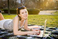 Pretty red hair woman working on laptop in park Stock Photography