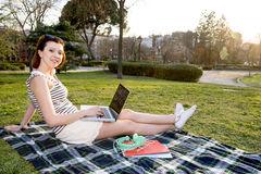 Pretty red hair woman working on laptop in park Stock Photos
