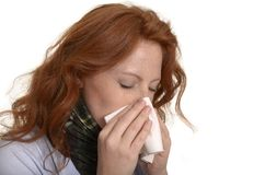 Pretty red-haired is cleaning her nose Royalty Free Stock Images
