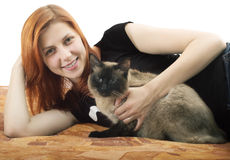 Pretty red-haired girl with a cat lying on the sofa Stock Image