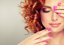 Pretty red haired girl with curls. Pretty red haired girl with curls , fashionable makeup and pink manicure. Close up portrait royalty free stock photo
