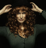 Pretty red-haired girl with curls with frackles, black hat Stock Image