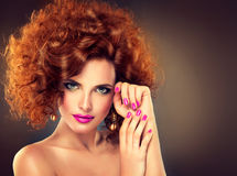 Pretty red haired girl with curls. Pretty red haired girl touching own furry hair.Fashionable makeup and pink manicure. Straight look on camera royalty free stock photos