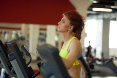 Pretty red-haired girl exercising on treadmill Stock Photography