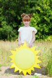 Pretty red-haired girl posing with paper sun Stock Photography