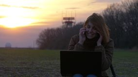 Pretty red-haired girl uses laptop and smartphone near communication radar. Young red-haired girl uses laptop and mobile phones and laugh near radar and stock video footage