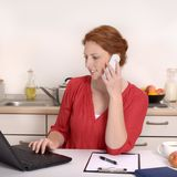 Pretty red haired Woman calling in Home Office. Studio Shot Royalty Free Stock Photos