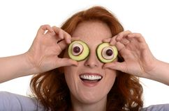 Pretty red-haired woman fooling around with vegetables Stock Image