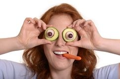 Pretty red-haired woman fooling around with vegetables Royalty Free Stock Image