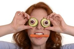 Pretty red-haired woman fooling around with vegetables Royalty Free Stock Images