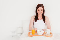 Pretty red-haired woman having her breakfast Stock Images