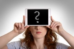 Pretty red-haired woman holding mini tablet pc with question mar Stock Image