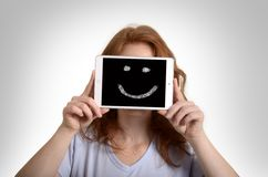 Pretty red-haired woman holding mini tablet pc with smiley Royalty Free Stock Image