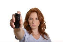 Pretty red-haired woman with pepper spray Royalty Free Stock Image