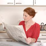 Pretty red haired woman reading newspaper Royalty Free Stock Image