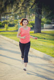 Pretty red haired woman running in the park Royalty Free Stock Photography