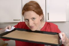 Pretty red haired woman shows empty baking tray, free copy space Royalty Free Stock Photography