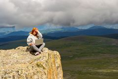 A pretty red-haired woman in sports clothes will work as a freelancer while traveling on the edge of a high mountain on stock photography