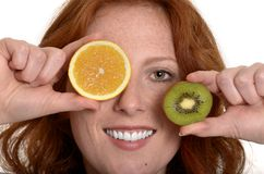 Pretty red-haired woman with tranches of fruits Royalty Free Stock Images