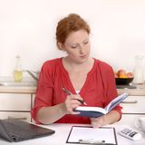 Pretty red haired Woman working in Home Office. Studio Shot Royalty Free Stock Image
