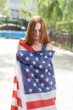 Pretty red haired women wrapped around with  US flag Royalty Free Stock Images