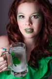 Pretty red headed woman drinking from a Mug with a shamrock on i Royalty Free Stock Photos