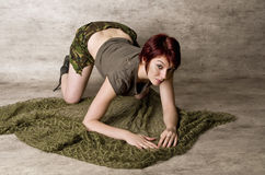Pretty Redhead in Camouflage. Pretty red haired woman in camouflage shorts kneeling on green fabric Stock Images