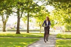 Pretty redhead cycling a bike Stock Photo