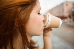 Pretty redhead drinking from disposable cup. In the street stock photography