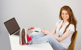 Pretty redhead with feet up on desk Royalty Free Stock Photo
